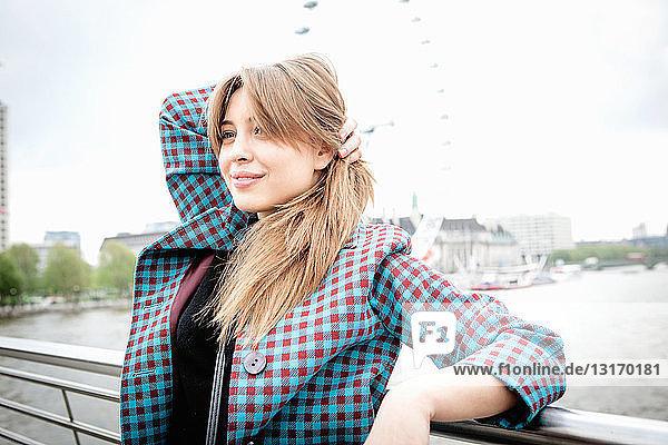 Junge Touristin lehnt an einem Geländer auf der Fußgängerbrücke zum Golden Jubilee  London  Großbritannien