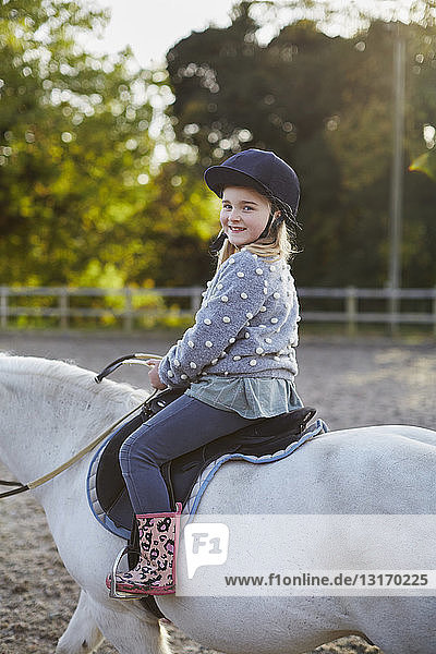 Portrait of happy girl riding white pony in equestrian arena