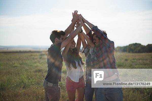 Vier Freunde halten Hände mit erhobenen Armen