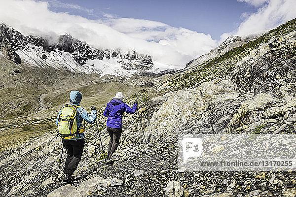 Zwei Wandererinnen wandern auf Felsen  Fil de Cassons  Segnesboden  Graubünden  Schweiz
