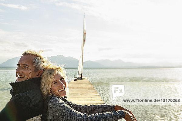 Reifes Paar auf dem Steg  Rücken an Rücken sitzend  lächelnd