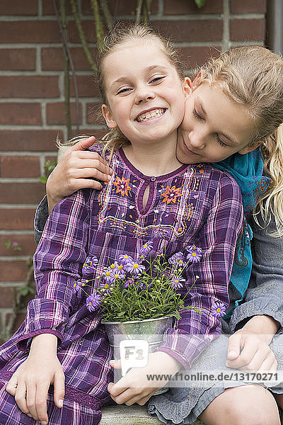 Two sisters with flower pot plant in garden