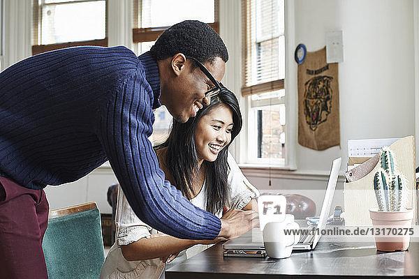 Junges Paar benutzt Laptop zu Hause