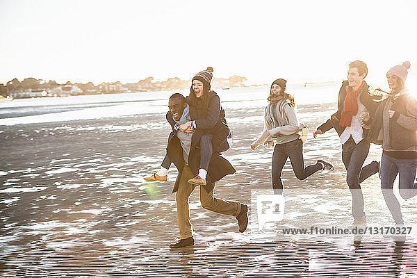 Fünf erwachsene Freunde laufen am Strand