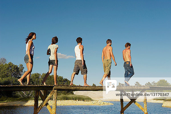 Group of young people walking on jetty