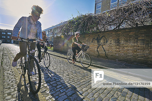 Angled view of women cycling on bicycles on cobblestone road