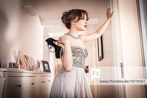 Müde junge Frau im Abendkleid im Flur