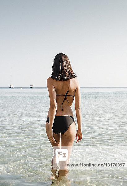 Rear view of young woman wearing bikini paddling in sea