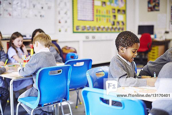 Children drawing at desks in elementary school classroom