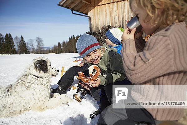 Kinder mit Brezelpause und warmem Getränk im Schnee
