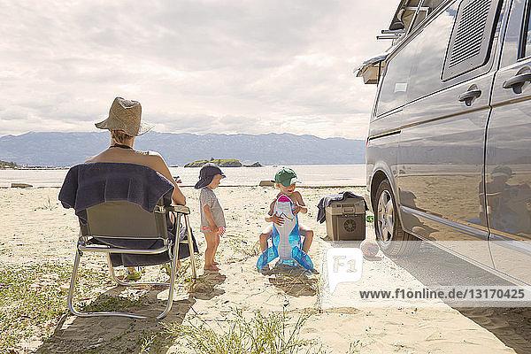 Rückansicht einer reifen Frau und zweier Söhne am Strand  Lopar  Insel Rab  Kroatien