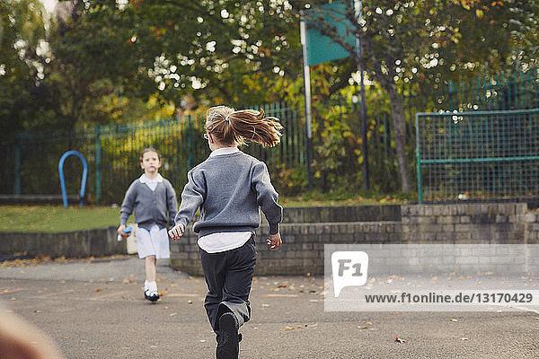 Elementary schoolgirls running in playground