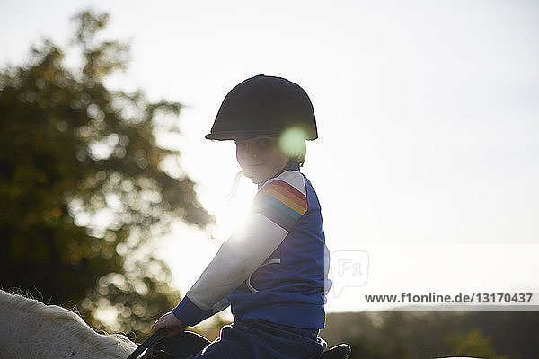 Portrait of boy riding pony in equestrian arena