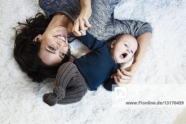 Mutter auf Teppich liegend mit kleinem Sohn  Draufsicht