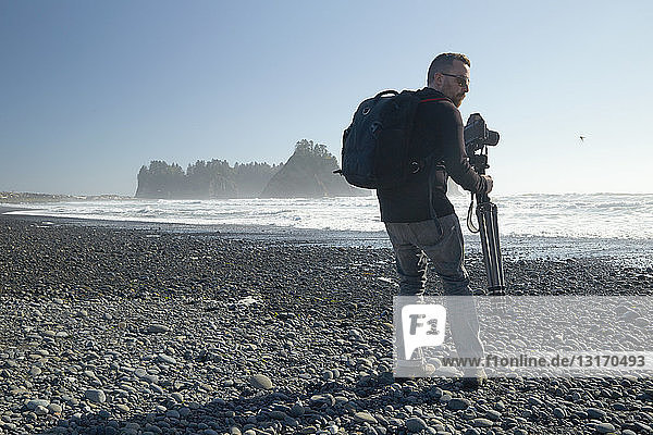 Male photographer on beach carrying camera and tripod,  Rialto Beach,  Washington State,  USA