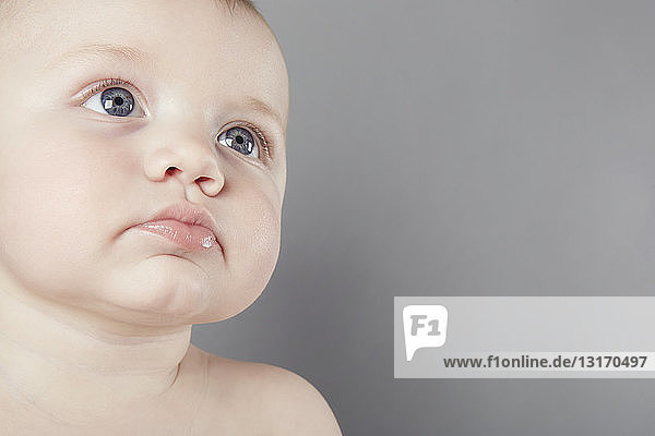 Cropped studio portrait of baby boy with sad face