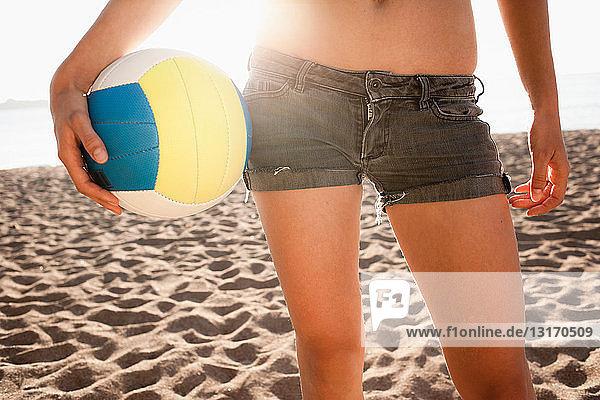 Frau hält Volleyball am Strand