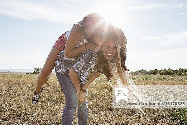 Junge Frau gibt Freundin Huckepack