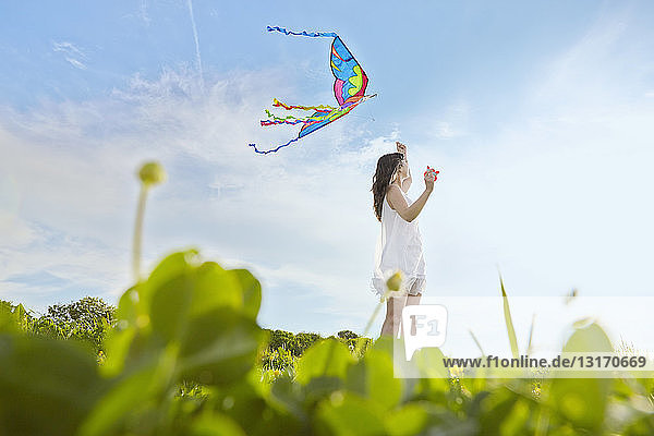 Surface level view of young woman flying a kite in field