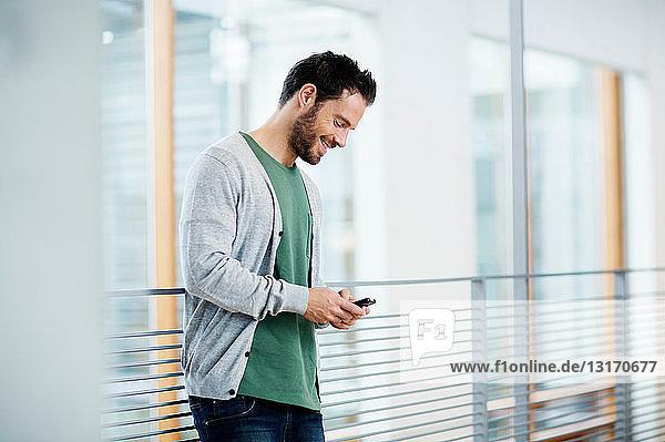 Mann schaut auf Mobiltelefon