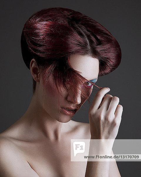 Porträt einer jungen Frau mit gestyltem Haar  die ihre Haare über das Gesicht zieht