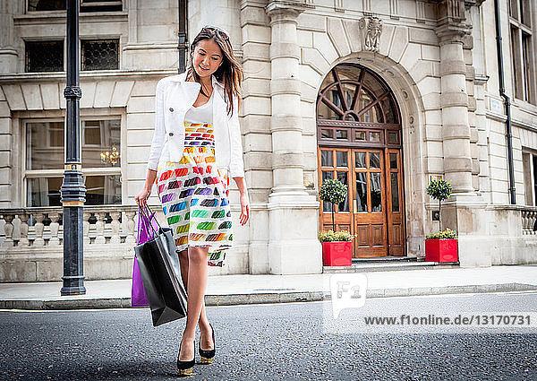 Junge Frau geht in London auf der Straße und trägt Einkaufstaschen