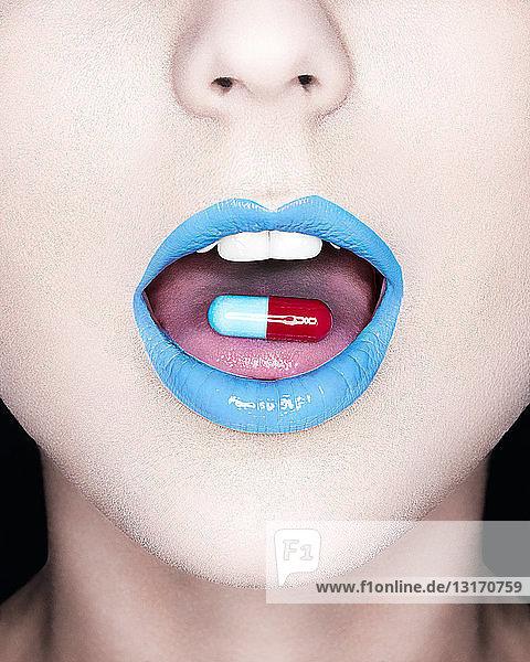 Nahaufnahme des Mundes der Frau mit hellem Lippenstift und Pille