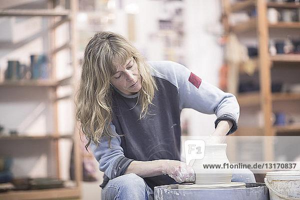 Töpferin formt Tontopf auf Töpferscheibe in der Werkstatt