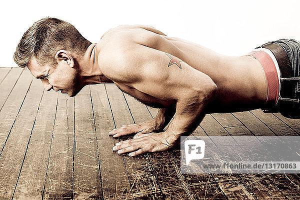 Mittelgroßer erwachsener Mann macht Liegestütze auf Holzboden