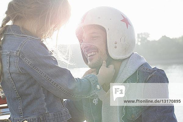 Junges Mädchen hilft ihrem Vater beim Aufsetzen des Sturzhelms