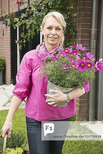 Portrait of mature woman carrying pink flower pot plant in garden