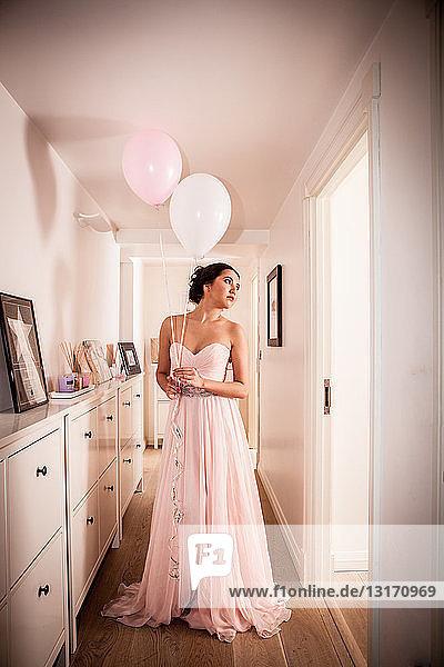 Junge Frau im Abendkleid träumt im Flur