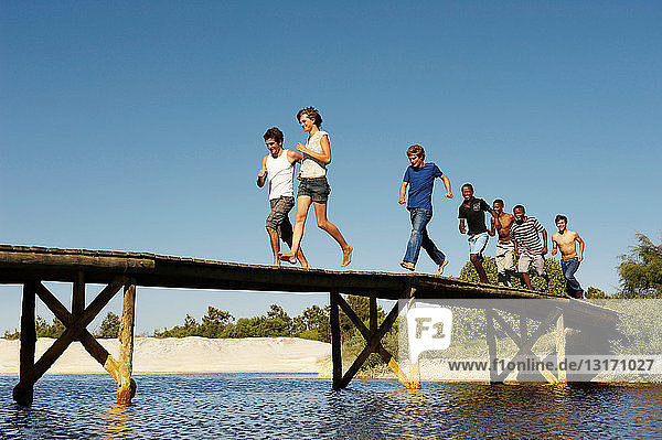 Group of teenagers running across jetty