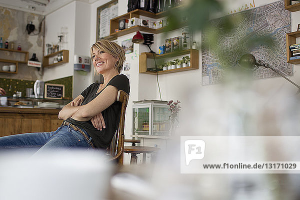 Mittlere erwachsene Frau  die im Café sitzt