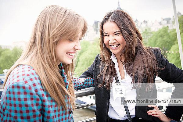 Zwei junge Touristinnen kichern auf der Fußgängerbrücke des Golden Jubilee  London  UK