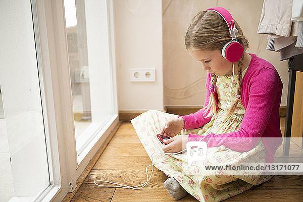 Girl sitting on floor selecting music for headphones