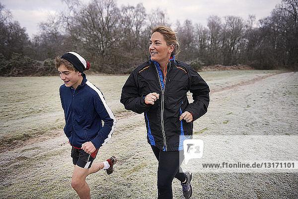 Mutter und Sohn rennen auf frostigem Grasland und schauen lächelnd weg