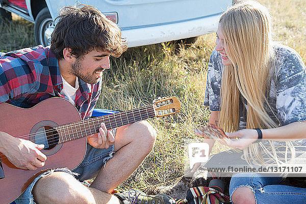 Junger Mann spielt Gitarre für junge Frau