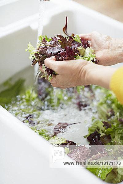 Frau wäscht Gemüse in der Küchenspüle