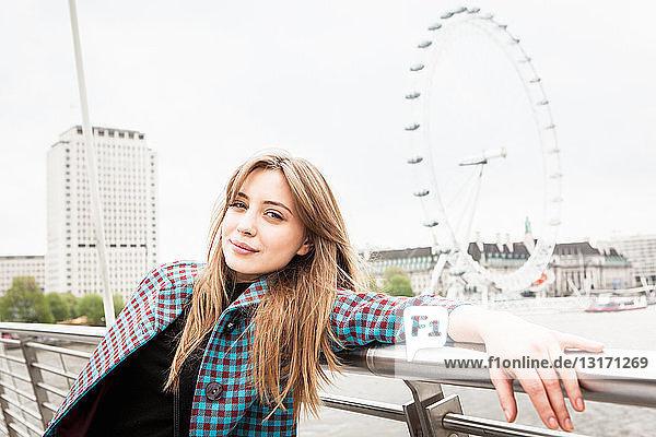 Porträt einer jungen Touristin  die auf der Fußgängerbrücke zum Golden Jubilee posiert  London  Großbritannien
