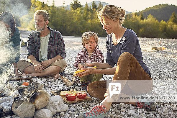 Junge sitzt am Lagerfeuer und beobachtet reife Frau bei der Essenszubereitung