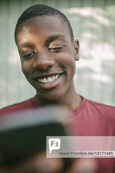 Lächelnder Junge benutzt Handy im Hinterhof