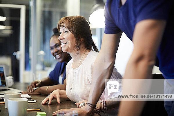 Lächelnde Mitarbeiter am Konferenztisch im Kreativbüro