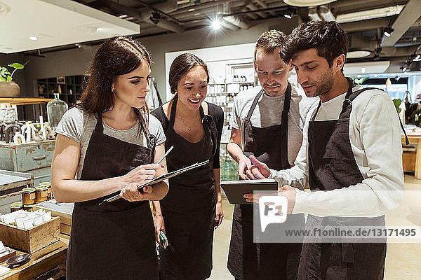 Männliche und weibliche Kollegen diskutieren über digitale Tablets im Geschäft