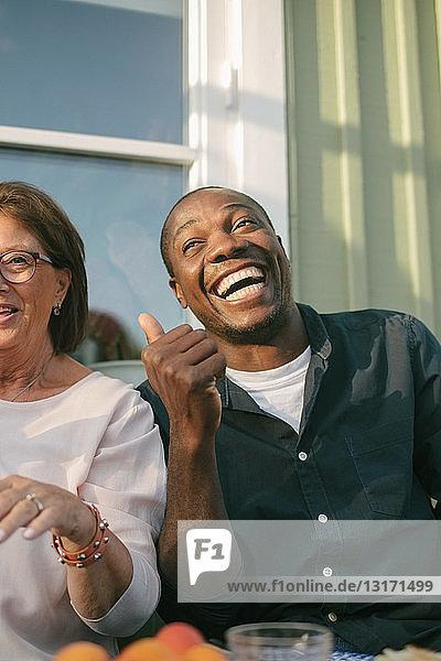 Glückliche ältere Frau sitzt neben einem Mann auf der Veranda