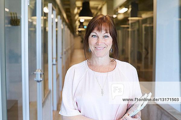 Porträt einer selbstbewussten Geschäftsfrau  die ein Spiral-Notizbuch hält  während sie im Bürokorridor steht