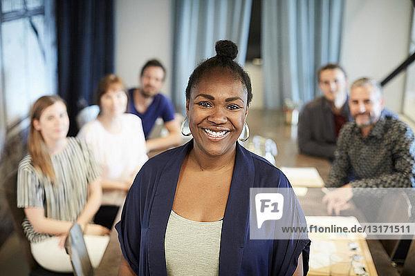 Porträt einer selbstbewussten Geschäftsfrau  die steht  während ihre Kollegen im Hintergrund im Büro arbeiten