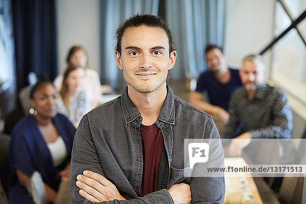 Porträt eines selbstbewussten Geschäftsmannes im Stehen  während Kollegen im Hintergrund im Kreativbüro arbeiten