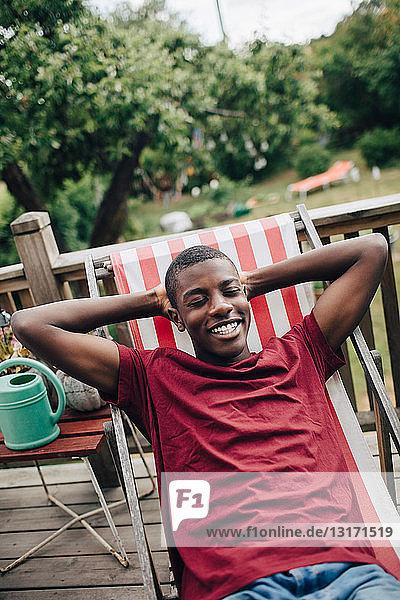 Lächelnder Junge entspannt auf Liegestuhl auf der Veranda