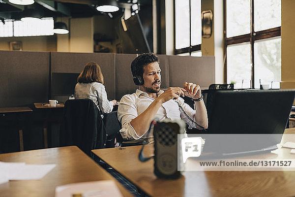 Kreativer Geschäftsmann mit Kopfhörern bei Videokonferenzen am Laptop im Büro